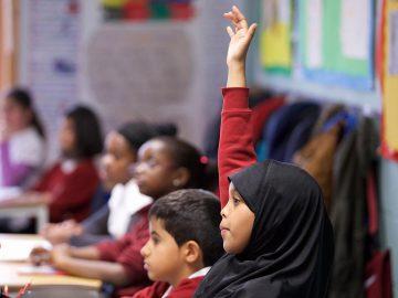 Primary school pupil child raising hand