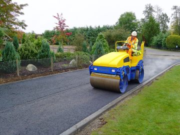 Man driving steam-roller on concrete