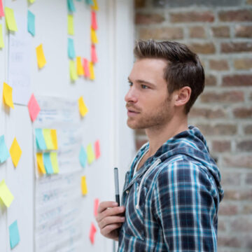 Young man in casual clothes looking at notice board